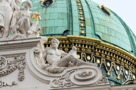 36291932 - white baroque sculpture of a man on the roof of a historic building on a background of green dome in vienna, austria