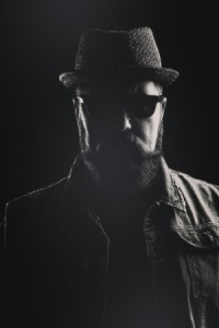 52173412 - vertical portrait of a hipster with a pork pie hat and a thick beard against a black background