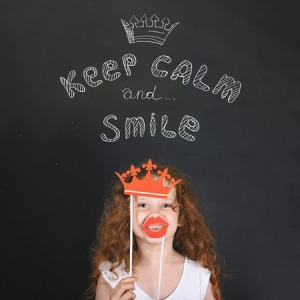 65197135 - funny girl with carnival crown and lips showing her teeth, standing beside chalkboard. keep calm and smile. happy childhood, healthy smile concept.