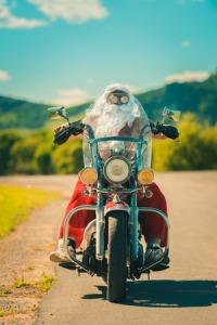 62177462 - sunburned santa biker riding motorcycle on summer vacations